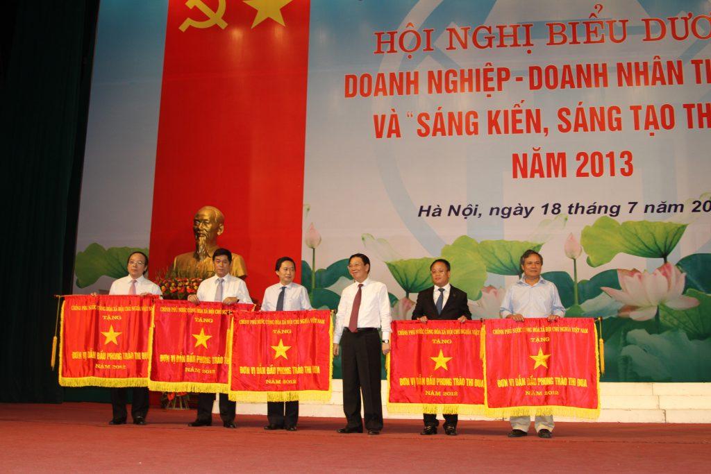 PGS. TS Đinh Văn Thuân (bên phải) nhận Cờ Chính phủ tặng Tập đoàn POLYCO